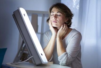 woman-sitting-at-light-therapy-box.jpg